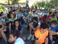 Participantes sentados a la sombra de los arboles
