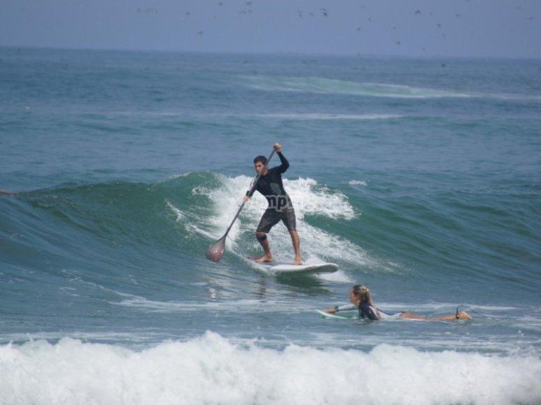Surcando una ola a bordo de una tabla de paddle surf