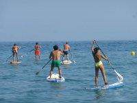 Varias personas probando el paddle surf