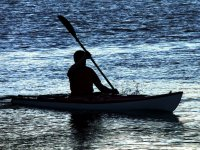 silhouette of a man rowing a canoe