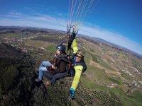 Instructor de parapente con pasajera en Portugal