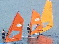 Three girls sailing on windsurfing