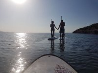 Couple doing sup at sunset