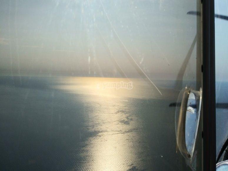 Reflejo del sol en el mar bajo la avioneta