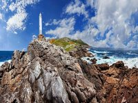 view of a lighthouse between the mountains with the sea and the background clouds