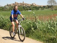 女孩骑自行车带村背景