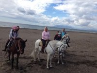 familia paseando a caballo por la playa