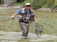 hombre saliendo del rio tras su pesca