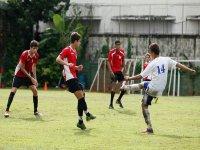 jovenes jugando al futbol en un campo de futbol