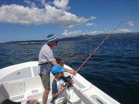 Padre e hijo pescando en el barco