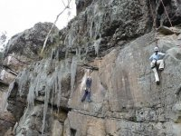 dos personas escalando por una pared vertical
