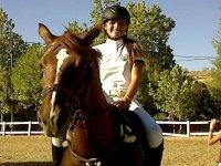 joven sonriente montando a caballo