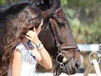 mujer junto a la cabeza de un caballo