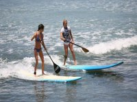 board two girls catching the waves practicing paddle surfing