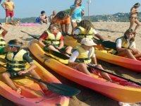 ninos subidos en unos kayaks