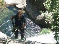 hombre haciendo rapel con el agua de fondo