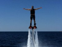 uomo con le braccia alzate facendo flyboard