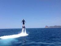 praticando flyboard con le montagne sullo sfondo