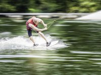man sliding down the water on a ski board