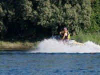 男孩用水摩托车捕捉波浪