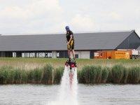hombre practicando flyboard con vegetacion de fondo