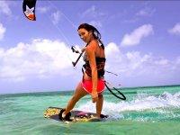 Chica haciendo kite en aguas turquesas