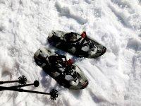 网球拍雪鞋的脚走在雪地