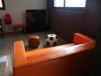 sofa naranja con dos pubs en el suelo.JPG