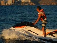 de pie en una moto de agua con benidorm de fondo