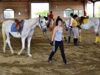 Chicas con los caballos en pista cubierta de el Catllar