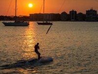 practicando wakeboard con dos barcos de fondo en un atardecer