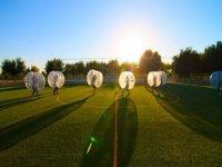 en un atardecer jugando al futbol en unas pelotas gigantes