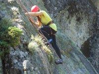 chica practicando escalada en una roca natural