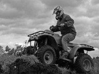 hombre en un quad por un terreno montanoso