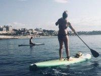 En pie sobre la tabla de paddle surf