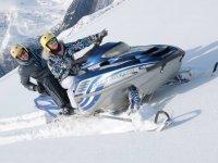 Abrigada pilotando la moto de nieve