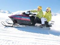 Con cascos amarillos en la moto de nieve