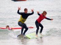 Alumno y profe de surf sobre la ola