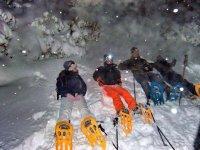 Sentados sobre la nieve con las raquetas