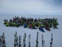 Alumnos saludando tumbados en la nieve