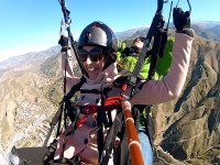 Enjoying the paragliding flight with a pink jacket