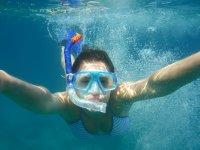 Chica haciendo snorkel con gafas