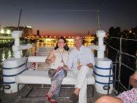 Pareja paseando en barco de noche por Sevilla