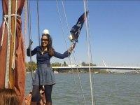 Sevillana sosteniendo la bandera en el barco