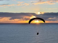 Paragliding over the sea with the sunset