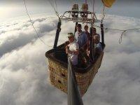 Pasajeros en globo sobre las nubes