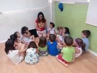 老师坐在孩子们用色彩玩