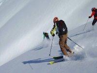 Descendiendo la montaña nevada con los esquís
