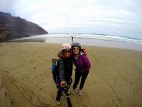 Pasajera y piloto de parapente en la playa