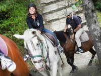 Joven amazona sonriendo sobre el caballo